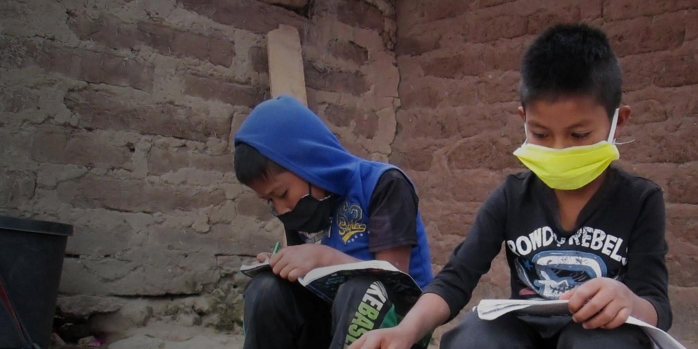 dos niños con cuadernos leyendo y escribiendo